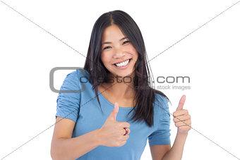 Smiling asian woman giving thumbs up at camera