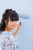 Cute woman painting wall blue and smiling at camera
