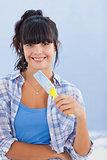 Pretty woman holding paint brush smiling at camera