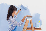 Woman using paint roller to paint wall