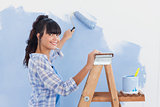 Woman using paint roller to paint wall and smiling at camera