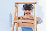 Smiling woman holding paint roller leaning on ladder