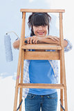 Happy woman holding paint roller leaning on ladder