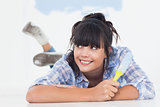 Smiling woman lying on floor holding paint brush