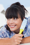 Cute woman lying on floor holding paint brush