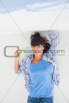 Attractive woman lying on floor holding paint brush overhead