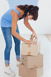 Brunette taping up moving boxes