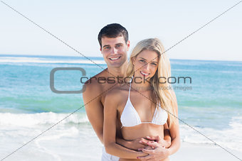 Gorgeous couple embracing and smiling at camera