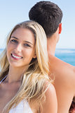 Pretty blonde smiling and leaning against her boyfriend