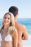 Happy blonde smiling and leaning against her boyfriend