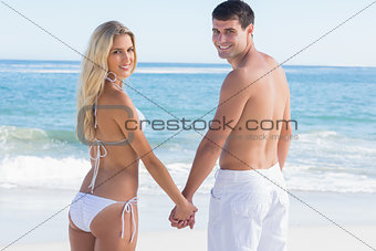 Rear view of couple holding hands looking at camera