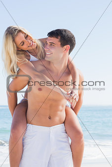 Happy man giving his pretty girlfriend a piggy back