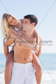 Happy man giving his pretty girlfriend a piggy back