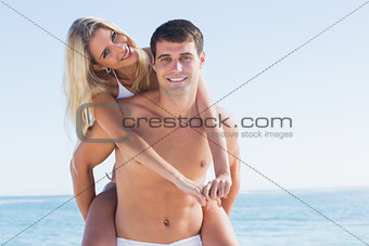 Happy man giving his pretty girlfriend a piggy back smiling at camera