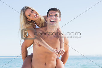 Laughing man giving his pretty girlfriend a piggy back smiling at camera