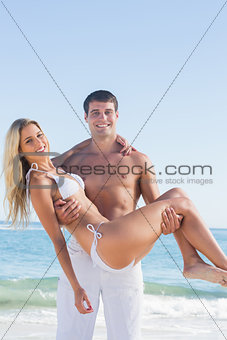 Strong man carrying his pretty girlfriend smiling at camera