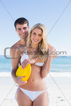 Man holding frisbee and embracing his girlfriend