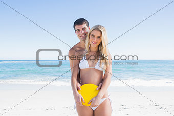 Man holding frisbee and embracing his girlfriend smiling at camera