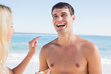 Woman putting sun cream on boyfriends nose