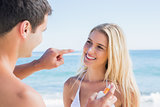 Man putting sun cream on smiling girlfriends nose