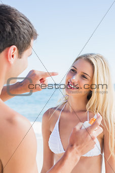 Man putting sun cream on cute girlfriends nose
