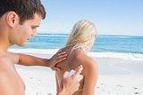 Man putting sun cream on girlfriends back