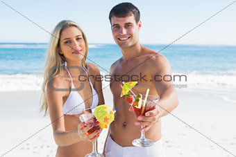 Beautiful young couple smiling at camera holding cocktails