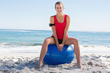 Fit young blonde sitting on exercise ball smiling at camera
