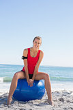 Fit blonde sitting on exercise ball smiling at camera