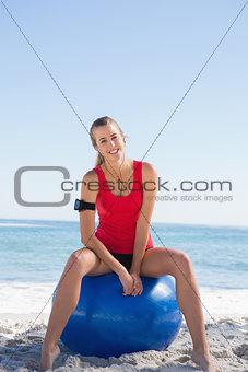 Fit woman sitting on exercise ball smiling at camera