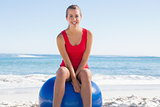 Fit young woman sitting on exercise ball smiling at camera