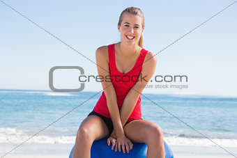 Fit young woman sitting on exercise ball looking at camera