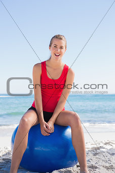 Fit happy woman sitting on exercise ball looking at camera