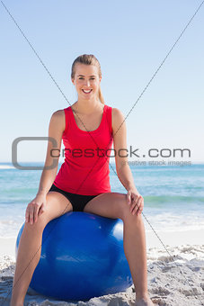 Happy woman sitting on exercise ball looking at camera