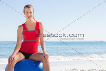 Athletic woman sitting on exercise ball looking at camera