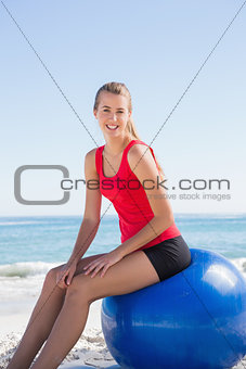 Athletic young blonde sitting on exercise ball looking at camera