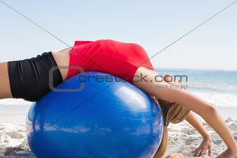 Fit blonde stretching back on exercise ball