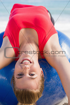 Fit blonde stretching back on exercise ball looking at camera