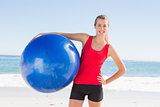 Fit blonde holding exercise ball smiling at camera