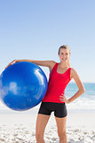 Fit blonde woman holding exercise ball