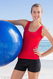 Fit woman holding exercise ball smiling at camera