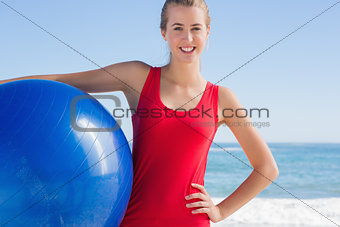 Fit blonde holding exercise ball looking at camera