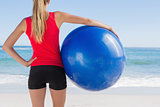 Fit blonde holding exercise ball looking at sea
