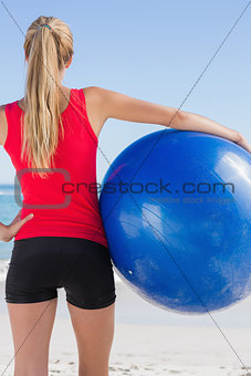 Fit blonde holding exercise ball looking at ocean