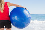 Fit blonde holding exercise ball looking at waves