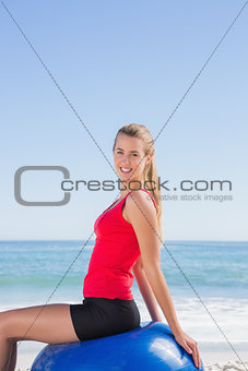 Cheerful woman sitting on exercise ball looking at camera