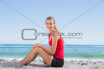 Fit blonde sitting on sand smiling at camera