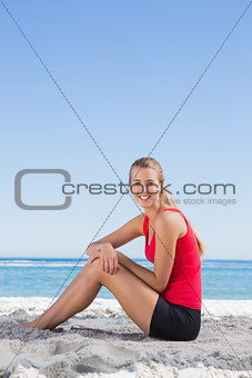 Athletic blonde sitting on sand smiling at camera