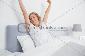 Blonde woman stretching and smiling in bed in the morning
