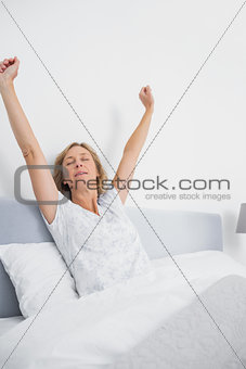 Blonde woman stretching in bed in the morning